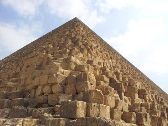 Three pyramids stand on a desert rock zone